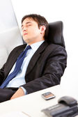 Tired businessman sleeping on office armchair — Stock Photo