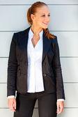 Sonriente mujer de negocios junto a edificio de oficinas y mirando de lado — Foto de Stock
