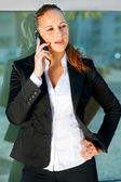 Pensive business woman talking on mobile near office building — Stock Photo