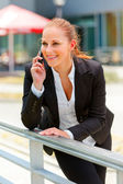 Smiling business woman leaning on railing and talking on mobile — Stock Photo