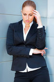 Pensive business woman with hand near head standing at office building — Stock Photo