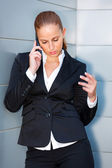 Concentrated business woman talking on mobile near office building — Stockfoto