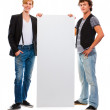 Two modern teenagers holding blank billboard. Isolated on white — Stock Photo