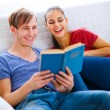 Stock Photo: Smiling young couple sitting on sofa with book
