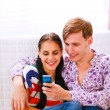 Royalty-Free Stock Photo: Young happy couple looking on cell phone