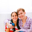 Stock Photo: Young smiling couple sitting on couch with mobile
