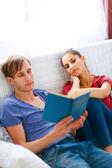 Flicka tråkig medan hennes pojkvän läsa bok — Stockfoto