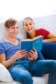 Smiling young couple sitting on sofa with book — Stock Photo