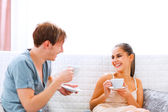 Young couple sitting at couch and drinking coffee — Stock Photo