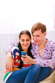 Young happy couple looking on cell phone — Stock Photo