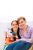 Young smiling couple sitting on couch with mobile — Stock Photo