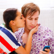 Girl trying to distract her busy boyfriend from mobile phone — Stock Photo