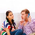 jonge man tonen shh... gebaar aan vriendin terwijl antwoordende m — Stockfoto #8630003