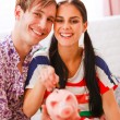 Portrait of happy young couple putting coin in piggy bank — Stock Photo #8630033