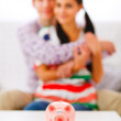 Piggy bank on table and happy young couple in background — Stock Photo