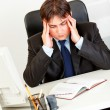Stressed businessman sitting at office desk holding his head and worrying — Stock Photo