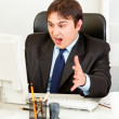 Shocked businessmsitting at office desk and looking at computer monitor — Stock Photo #8631578