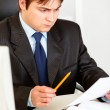 Serious businessman sitting at office desk and intently looking at document — Stock Photo #8631631