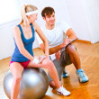 Smiling personal trainer helping his client — Stock Photo