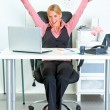 Excited business woman sitting at office desk and rejoicing her success — Stock Photo