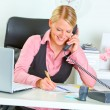 Smiling business woman talking phone and writing at notepad — Stock Photo