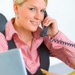 Smiling business woman sitting at office desk and talking on phone — Stock Photo