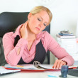 Tired business womsitting at office desk and working — Stock Photo #8634011