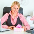 Happy modern business woman with present box at office desk — Stock Photo
