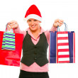 Smiling modern business woman in Santa Hat presenting shopping b — Stock Photo