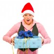 Surprised modern business woman in Santa Hat looking on gift — Stock Photo #8634505