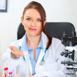 Royalty-Free Stock Photo: Doubting doctor woman showing on something