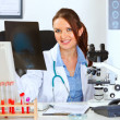 Stock Photo: Smiling female medical doctor sitting at office table with patie