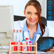 Happy doctor woman sitting at office table - Stock Photo