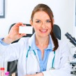 Smiling doctor woman sitting at office table and holding blank business car — Stock Photo #8636320