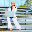 Smiling business woman sitting on stairs with laptop and talking — Stock Photo