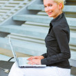 Stock Photo: Smiling business woman sitting on stairs at office building