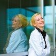 Stock Photo: Laughing business woman with crossed arms on chest at office building