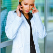 Strained business woman talking on mobile at office building — Stock Photo