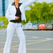 Smiling business woman catching taxi near office center — Stock Photo