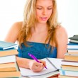 Girl sitting at table with lots of books and doing homework — Stock Photo