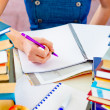 Girl sitting at table with lots of books and doing homework. Close up — Stock Photo