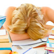 Tired teen girl sleeping at table with piles of books — Stock Photo #8638605