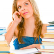 Teen girl sitting at table with books and dreamy looking in corner — Stock Photo
