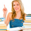 Smiling teengirl with rised finger sitting at table with books. Idea gestur — Stock Photo #8638621