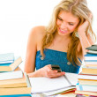 Smiling teen girl reading sms on mobile instead of doing homework — Stock Photo #8638626