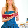 Pretty girl standing near table and reading book — Stock Photo #8638653