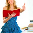 Smiling girl with book in hand standing near table and showing thumbs up ge — Stock Photo #8638658