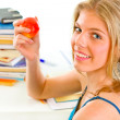 Smiling teen girl sitting at desk with books and holding apple in hand — Stock Photo