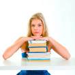 Concentrated girl sitting at desk and holding hands on piles of — Stock Photo