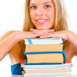 Smiling girl sitting at desk and holding hands on piles of books — Stock Photo